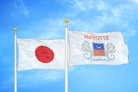 Japan and Mayotte two flags on flagpoles and blue cloudy sky background