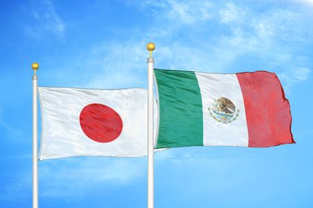 Japan and Mexico two flags on flagpoles and blue cloudy sky background