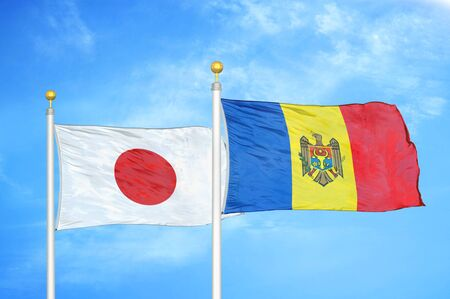 Japan and Moldova two flags on flagpoles and blue cloudy sky background