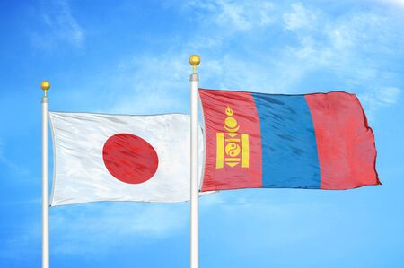 Japan and Mongolia two flags on flagpoles and blue cloudy sky background