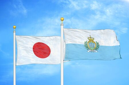 Japan and San Marino two flags on flagpoles and blue cloudy sky background