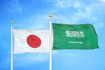Japan and Saudi Arabia two flags on flagpoles and blue cloudy sky background