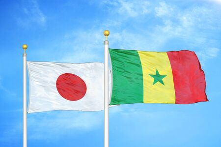 Japan and Senegal two flags on flagpoles and blue cloudy sky background Фото со стока