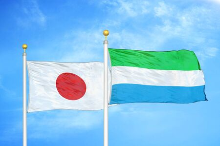 Japan and Sierra Leone two flags on flagpoles and blue cloudy sky background