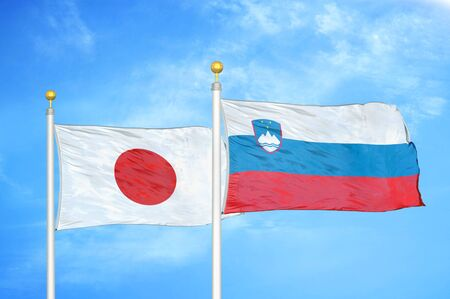 Japan and Slovenia two flags on flagpoles and blue cloudy sky background