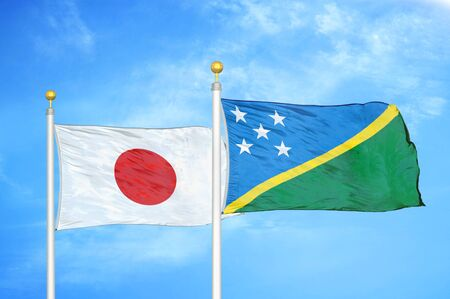 Japan and Solomon Islands two flags on flagpoles and blue cloudy sky background