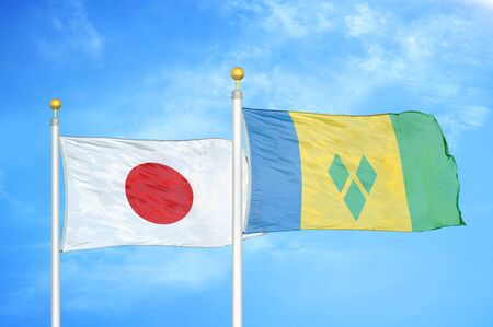 Japan and Saint Vincent and the Grenadines two flags on flagpoles and blue cloudy sky background