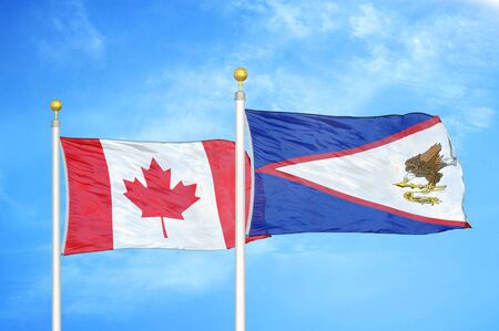 Canada and American Samoa two flags on flagpoles and blue cloudy sky background Stock Photo