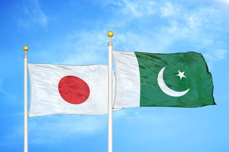 Japan and Pakistan two flags on flagpoles and blue cloudy sky background