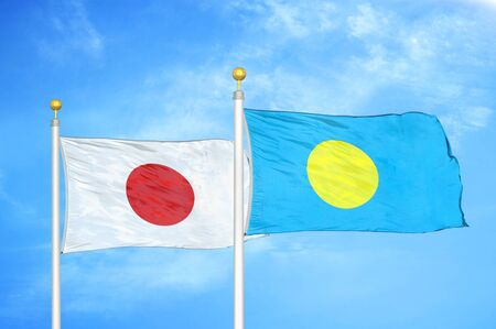 Japan and Palau two flags on flagpoles and blue cloudy sky background 스톡 콘텐츠
