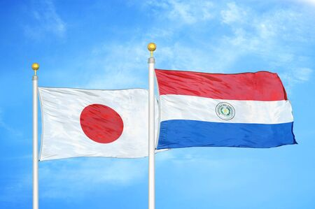 Japan and Paraguay two flags on flagpoles and blue cloudy sky background