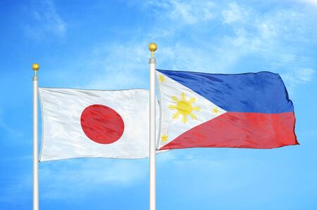Japan and Philippines two flags on flagpoles and blue cloudy sky background