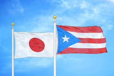 Japan and Puerto Rico two flags on flagpoles and blue cloudy sky background