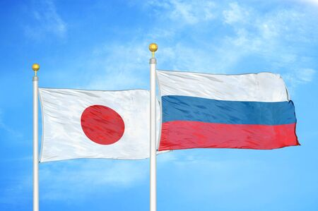 Japan and Russia two flags on flagpoles and blue cloudy sky background