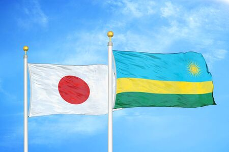 Japan and Rwanda two flags on flagpoles and blue cloudy sky background