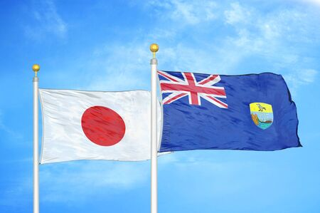 Japan and Saint Helena two flags on flagpoles and blue cloudy sky background