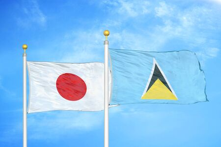 Japan and Saint Lucia two flags on flagpoles and blue cloudy sky background