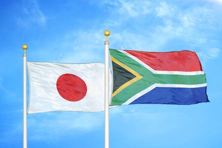 Japan and South Africa two flags on flagpoles and blue cloudy sky background