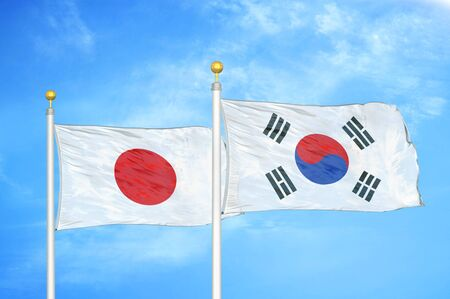 Japan and South Korea two flags on flagpoles and blue cloudy sky background