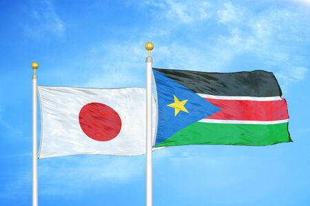 Japan and South Sudan two flags on flagpoles and blue cloudy sky background