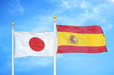 Japan and Spain two flags on flagpoles and blue cloudy sky background