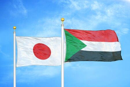 Japan and Sudan  two flags on flagpoles and blue cloudy sky background 스톡 콘텐츠