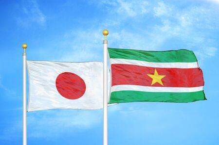 Japan and Suriname two flags on flagpoles and blue cloudy sky background