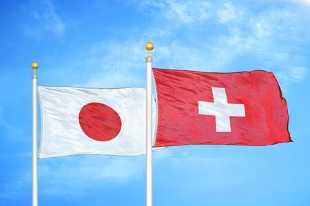 Japan and Switzerland two flags on flagpoles and blue cloudy sky background