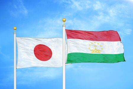 Japan and Tajikistan two flags on flagpoles and blue cloudy sky background
