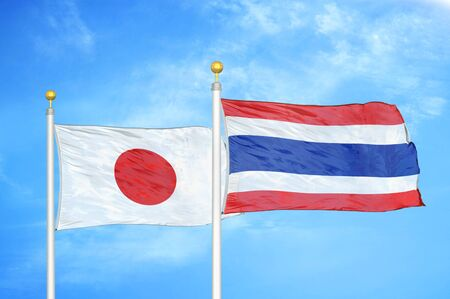 Japan and Thailand two flags on flagpoles and blue cloudy sky background