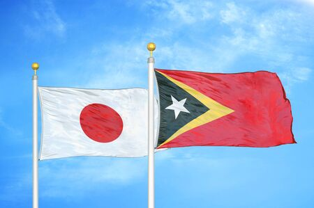 Japan and Timor-Leste East Timor two flags on flagpoles and blue cloudy sky background 스톡 콘텐츠
