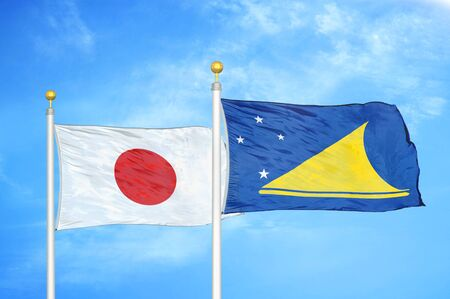 Japan and Tokelau two flags on flagpoles and blue cloudy sky background