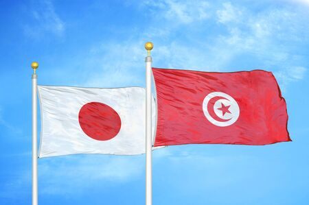 Japan and Tunisia two flags on flagpoles and blue cloudy sky background