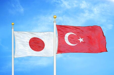 Japan and Turkey two flags on flagpoles and blue cloudy sky background