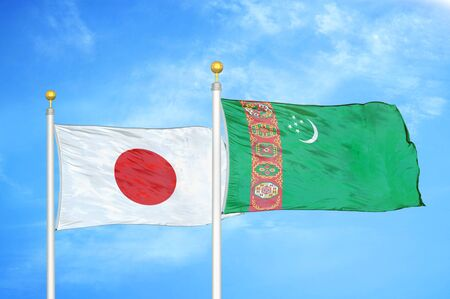 Japan and Turkmenistan two flags on flagpoles and blue cloudy sky background