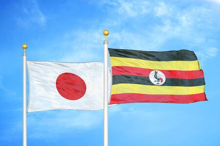 Japan and Uganda two flags on flagpoles and blue cloudy sky background