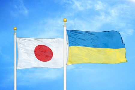 Japan and Ukraine two flags on flagpoles and blue cloudy sky background 스톡 콘텐츠