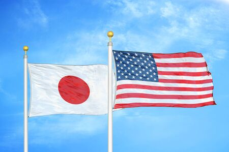Japan and United States two flags on flagpoles and blue cloudy sky background