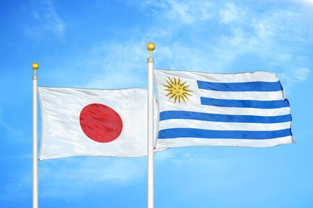 Japan and Uruguay two flags on flagpoles and blue cloudy sky background