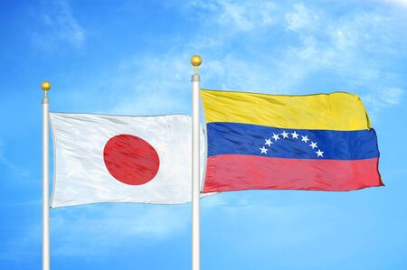 Japan and Venezuela two flags on flagpoles and blue cloudy sky background