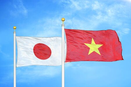 Japan and Vietnam two flags on flagpoles and blue cloudy sky background 스톡 콘텐츠