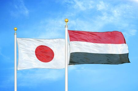 Japan and Yemen two flags on flagpoles and blue cloudy sky background