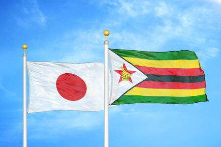Japan and Zimbabwe two flags on flagpoles and blue cloudy sky background