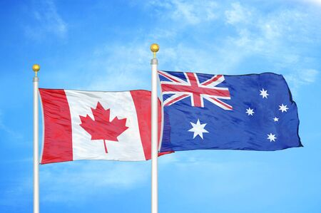 Canada and Australia two flags on flagpoles and blue cloudy sky background