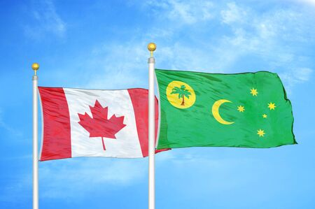 Canada and Cocos Keeling Islands two flags on flagpoles and blue cloudy sky background Stock Photo