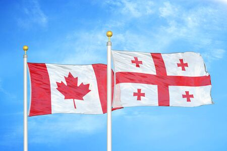 Canada and Georgia two flags on flagpoles and blue cloudy sky background
