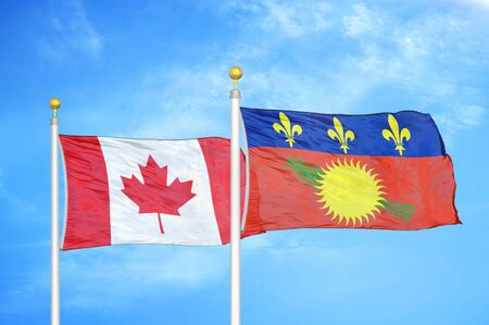 Canada and Guadeloupe two flags on flagpoles and blue cloudy sky background