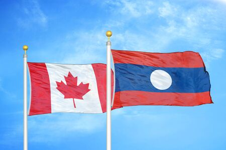Canada and Laos  two flags on flagpoles and blue cloudy sky background Stock Photo