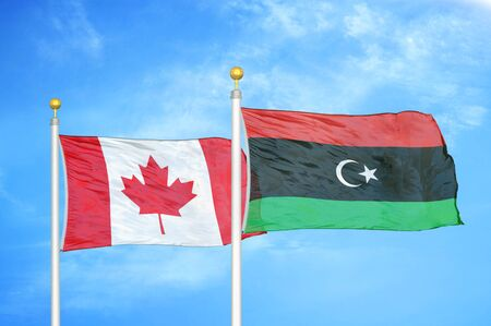 Canada and Libya two flags on flagpoles and blue cloudy sky background