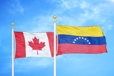 Canada and Venezuela two flags on flagpoles and blue cloudy sky background